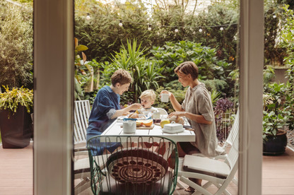 Mothers and their child having breakfast on their terrace