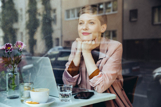 Woman sitting in café with laptop
