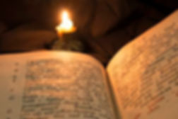 79920106-open-book-with-candle-soft-ligh
