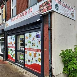 Corner shop sign with windows graphics