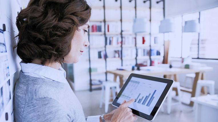 Na obrázku je hnědovlasá paní, která drží v levé ruce tablet. Studuje na něm grafy a statistiky.