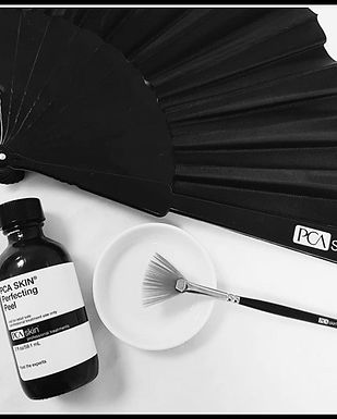Bottle of chemical peel solution, a brush and fan - perfecting peels at Alpha Aesthetics North Wales