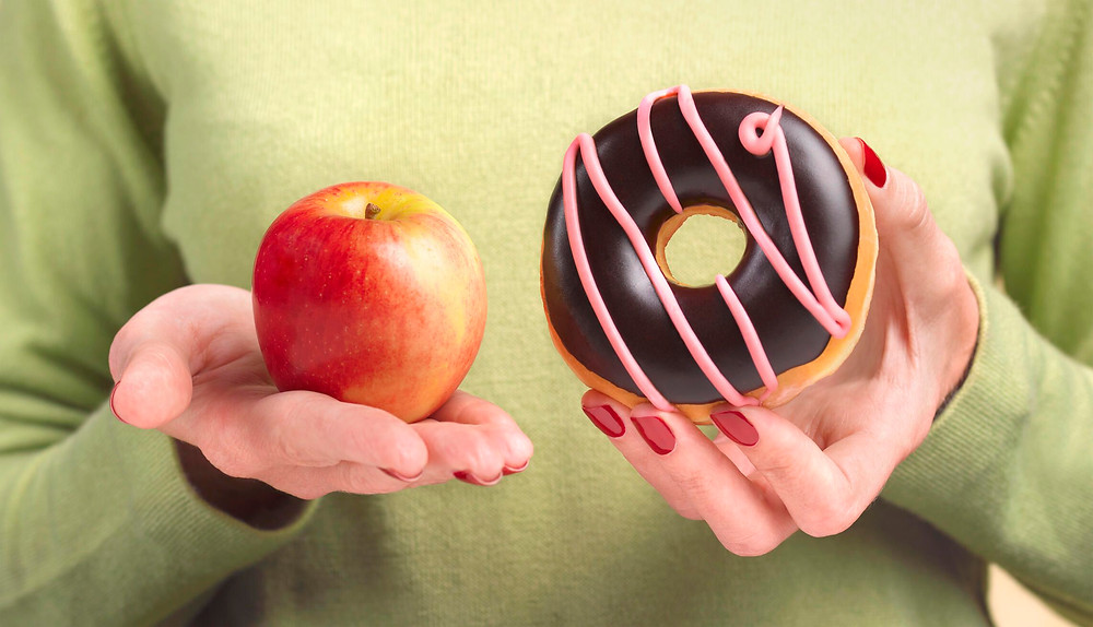 close-up of a woman holding an apple and a donut
