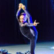 A junior Pom dancer peforming a leg mount