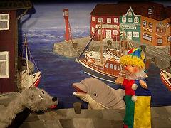 Kasperl und Strolchi lieben es, im Hafen herum zu tollen. Denn dort gibt es immer allerhand zu sehen. Und außerdem können sie dort auch ihren Freund Philip, den freundlichen Delfin, besuchen. So verbringen die beiden einen unbeschwerten Tag im Hafen, bis sich der Strolchi in einer leeren Kiste versteckt…