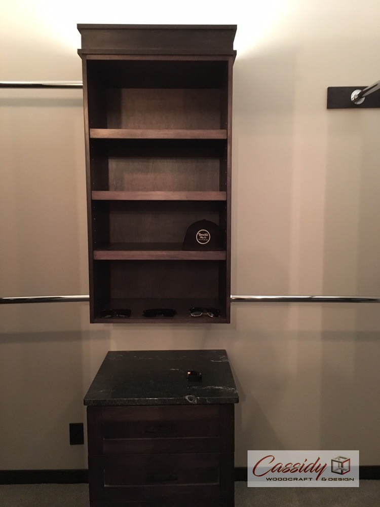 This custom walk-in closet features maple stained in black and includes ample storage for two, a make-up section and sliding barn door entry.