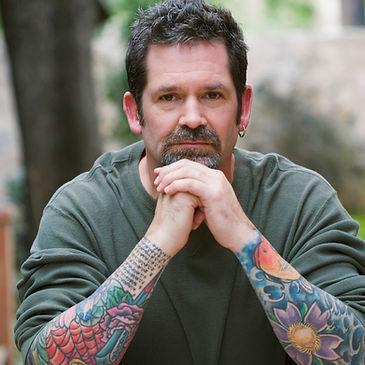 Homme tatoué d'âge moyen ayant les mains jointes sur le menton, fixe la caméra.