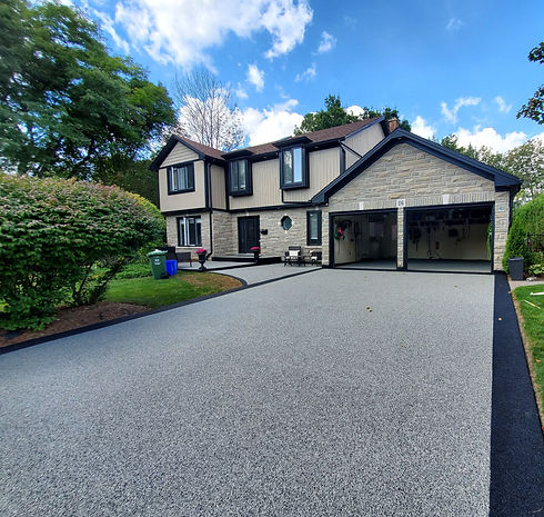Slip-resistant and crack-resistant rubber surfacing covered driveway, garage and porch in grey with black border to compliment stone house with black accents for beautiful, safe and durable surfacing