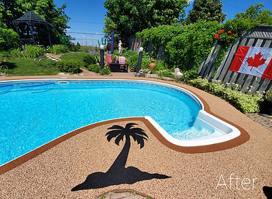 Brown rubber pool deck with a border around the pool and a black palm tree design in the rubber to match the lush greenery of the backyard