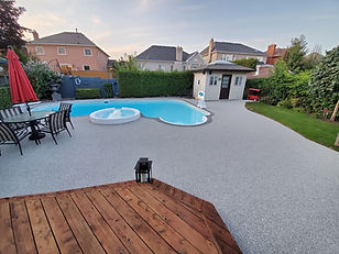 Large, backyard pool deck covered in light grey rubber for safe, non-slip surface
