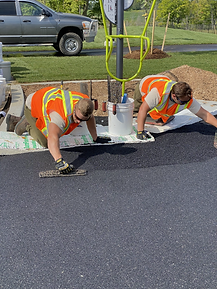 Black, recycled rubber base layer being trowelled on a playground