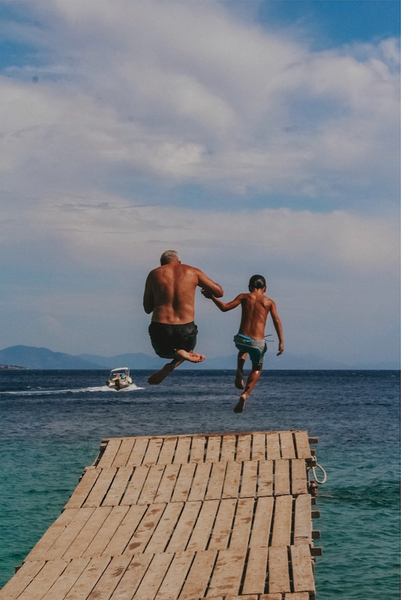 A shot from Kalami in Corfu. My family had hired a boat for the day and docked here for a drink. I decided to do some backflips off the side of the pier. We all ended up jumping off as a family one at a time, gathering some more people to join us, including this Greek family - a father and his son, who had jumped off multiple times separately. They decided to then jump together, holding hands, and I was so happy to have had my camera up at that moment.