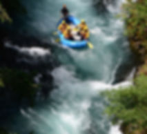 Three customers in a blue AIRE Tributary 14 #floatingonAIRE and wearing yellow helmets, life jackets and splash tops paddle into Rattlesnake rapids on the White Salmon River in Washington state.  They have paid for a commercial white water rafting trip with Portland Rafting Company and are being guided down the river with company owner Scott Cascella. 2018.