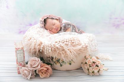 カゴで寝ている赤ちゃん。花の飾りでかわいい。