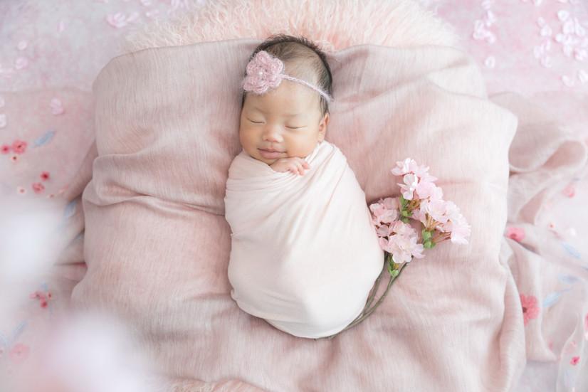 おくるみをして寝ている赤ちゃんの写真。ピンク色のクッションと花で飾っている。