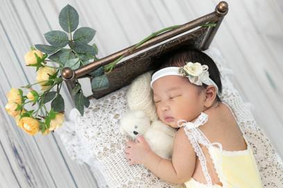 ぬいぐるみを抱っこしながら寝ている赤ちゃん。