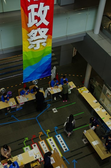 外濠校舎1階で入構チェックをする職員と学祭実委員。濃紺のジャンパーが職員、青のジャンパーが実行委員。