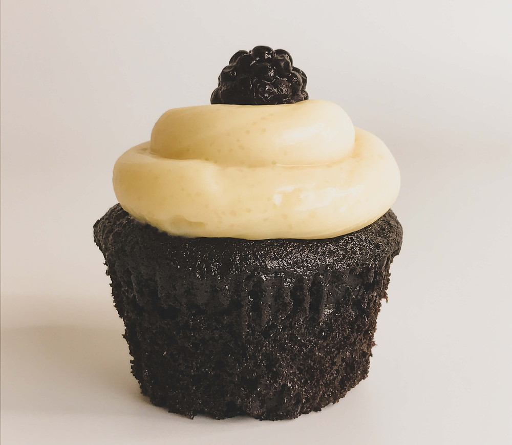 Chocolate cupcake with white chocolate frosting and blackberry topping