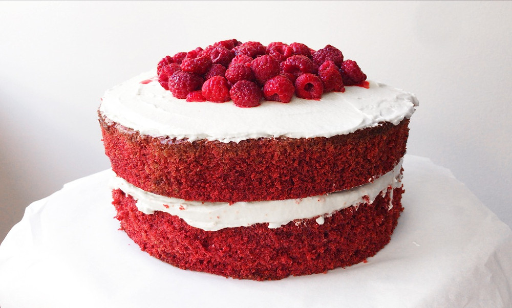 Two layer red velvet cake with cream cheese frosting and raspberries.