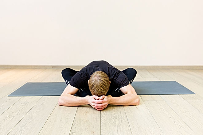 Sporty man practicing yoga on yoga class