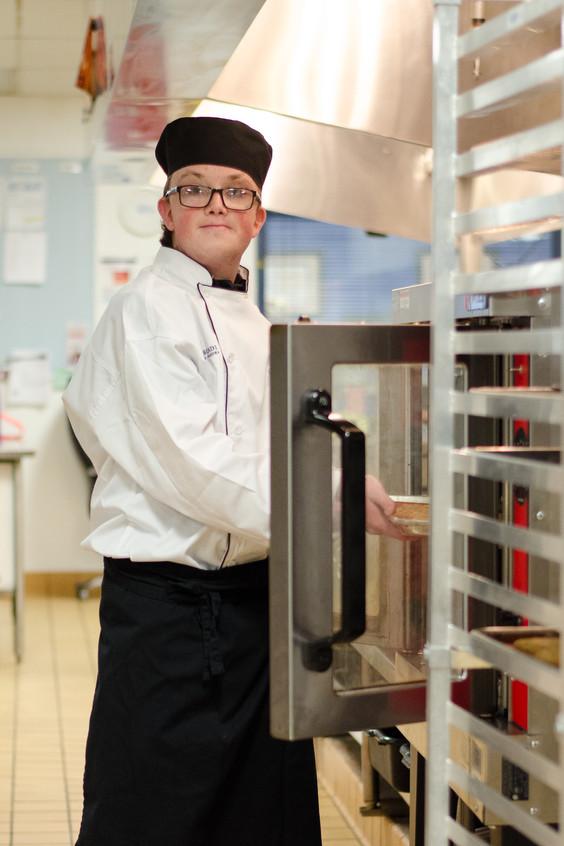 Logan placing cookies in the oven