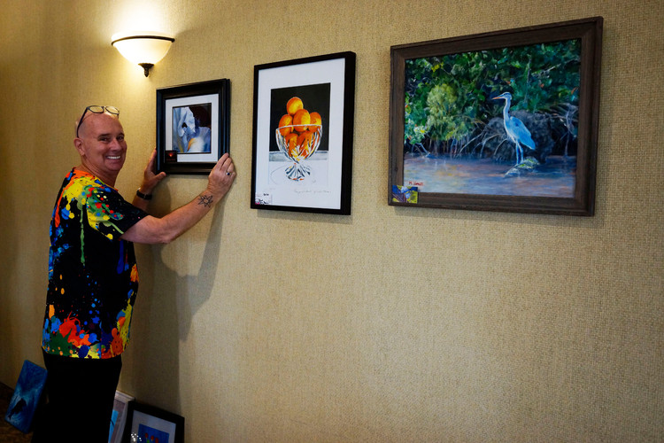 Phred Madsen- Vallee, curator, helps to hang artwork.