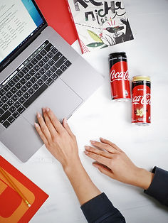 person-using-macbook-pro-beside-coca-col
