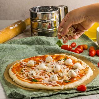 person-sprinkling-mozzarella-cheese-pizz