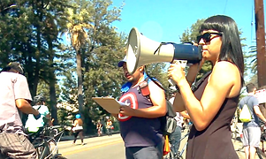 young woman holds a megaphone next to a cyclist