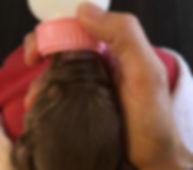 Newborn puppy being bottle fed