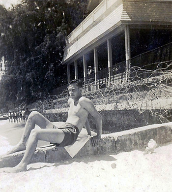 11. My dad sitting on the beach, ringed with barbed wire after the attack