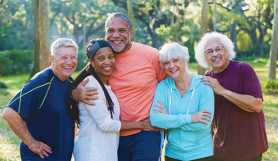 image of five older, smiling people in a park