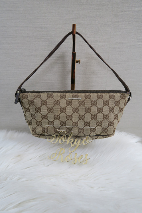 b64955dc3544 This small vintage handbag features. All over Gucci's classic GG logo monogram  canvas. Leather strap in the color dark brown
