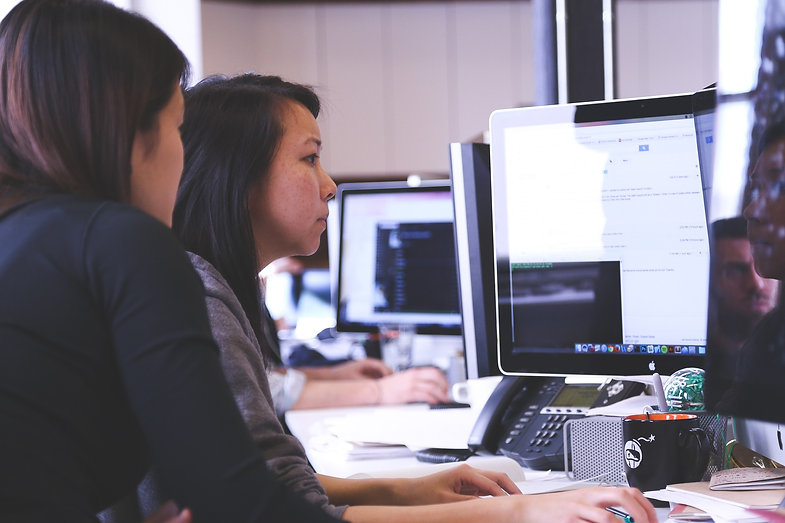 Two women doing work on an office computer
