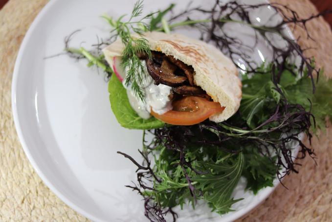 גירוס יווני מפטריות ושבבי סויה שהוקפצו על הפלנצ'ה. על פיתה עם ציזיקי קשיו וירקות