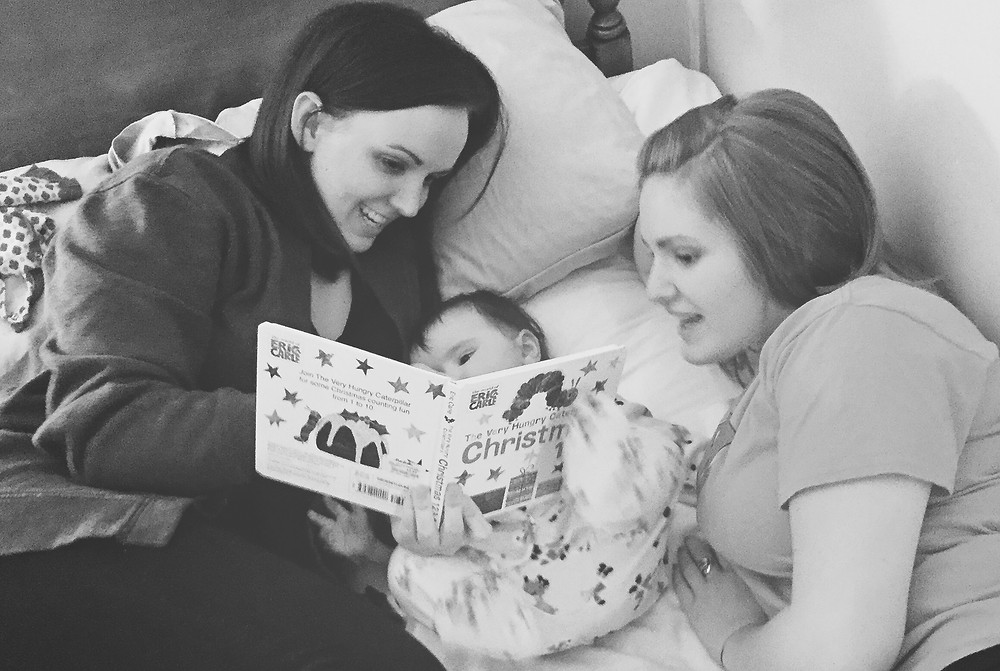 Christmas 2015, Emily and our sister Hannah read to my baby daughter