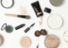 Powder, eyeshadow, foundation, and brushes scattered on table