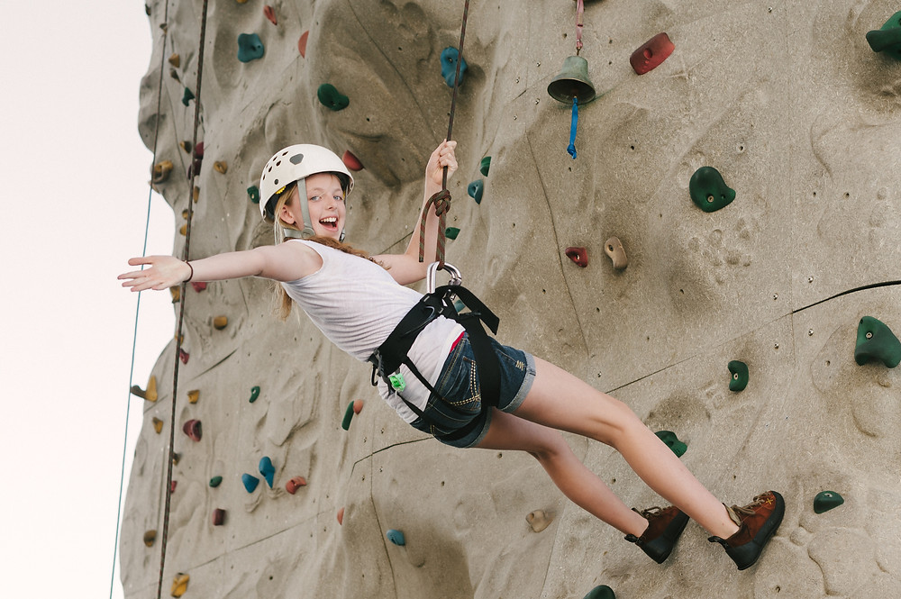 Young girl smiling and waving while rock climbing for the first time on an indoor rock climbing az gym