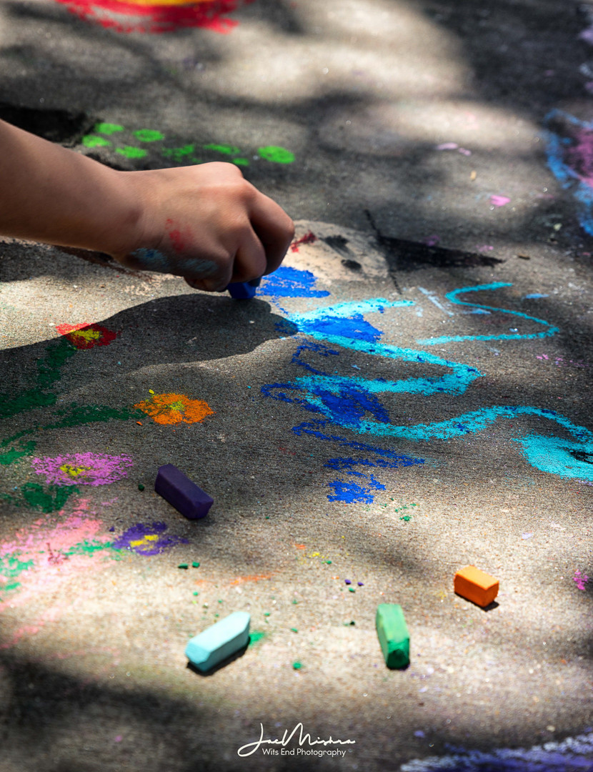 Photo child drawing on sidewalk with colorful chalk