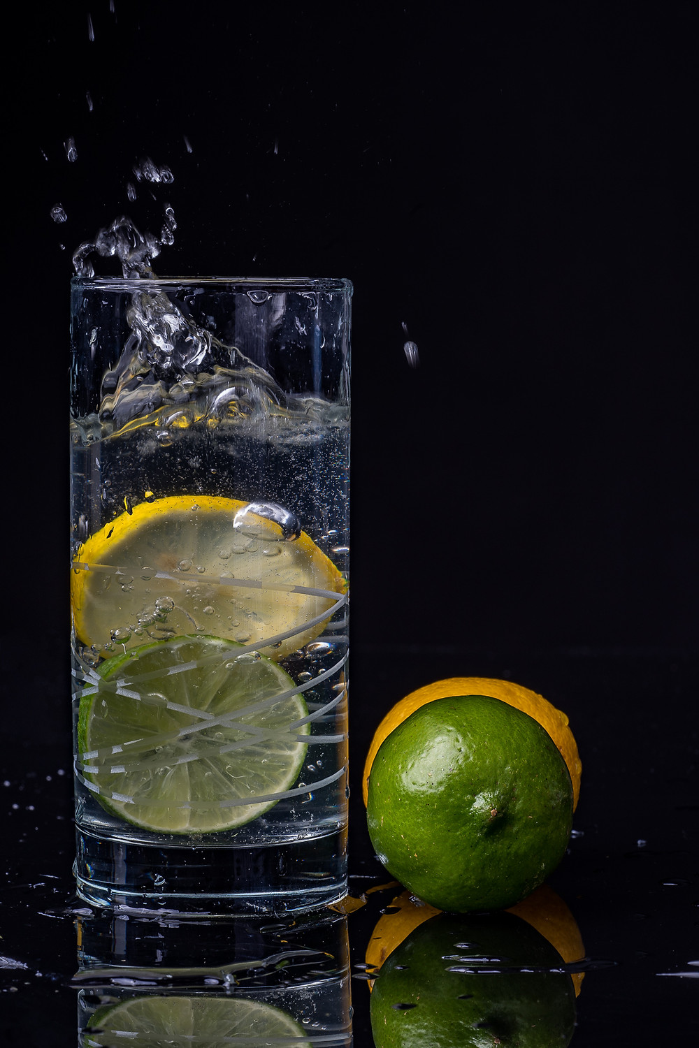 lemon limes splashed in glass of water