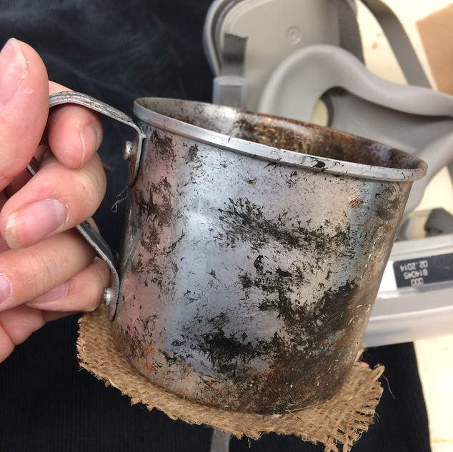 Tin cups that I dented and distressed in order to create a worn and rusty look. I dry brushed paint to create the visual textures seen.