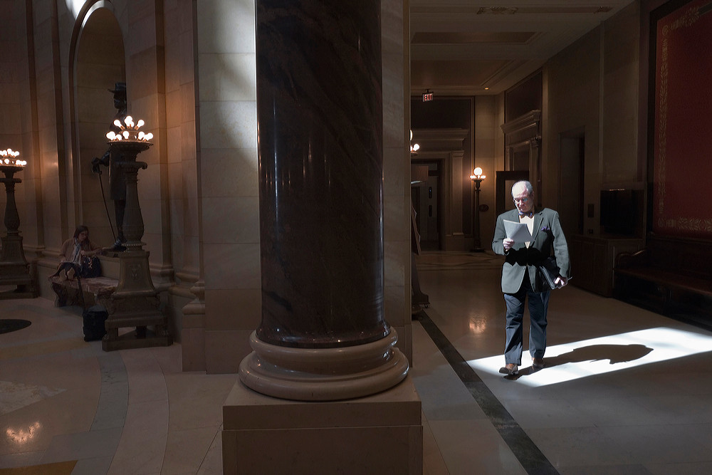 Shawn Towle, of Checks & Balances, passes through a beam of light just off the House Chamber as he scans a document he picked up in the Chief Clerks Office.