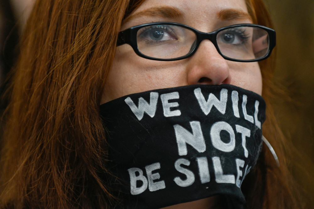 Amanda Wolfson wears her message while joining other protesters in opposition to two bills that would increase the penalties for obstructing highway and airport traffic access during a hearing of the House Public Safety and Security Policy and Finance Committee.