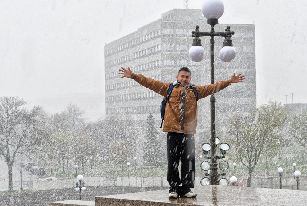 A participant in the Day Without Immigrants shows his youthful enthusiasm during a heavy snowfall after a rally in the Capitol Rotunda.