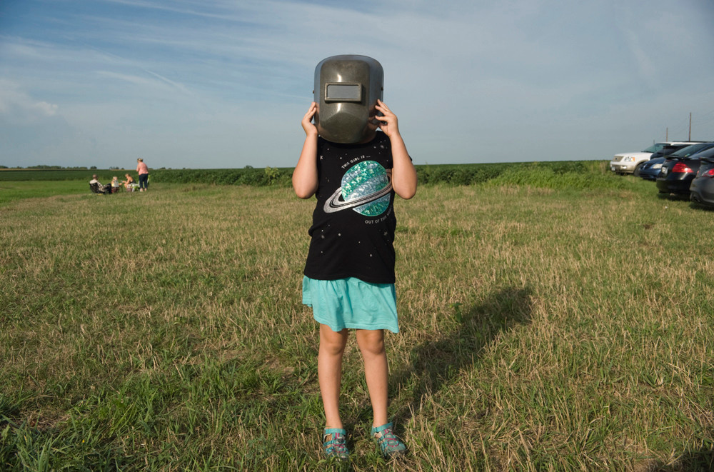 After arriving at the Homestead National Monument of America in Beatrice, Nebraska, a young girl checks to see how good a welder's helmet is for viewing the total solar eclipse.