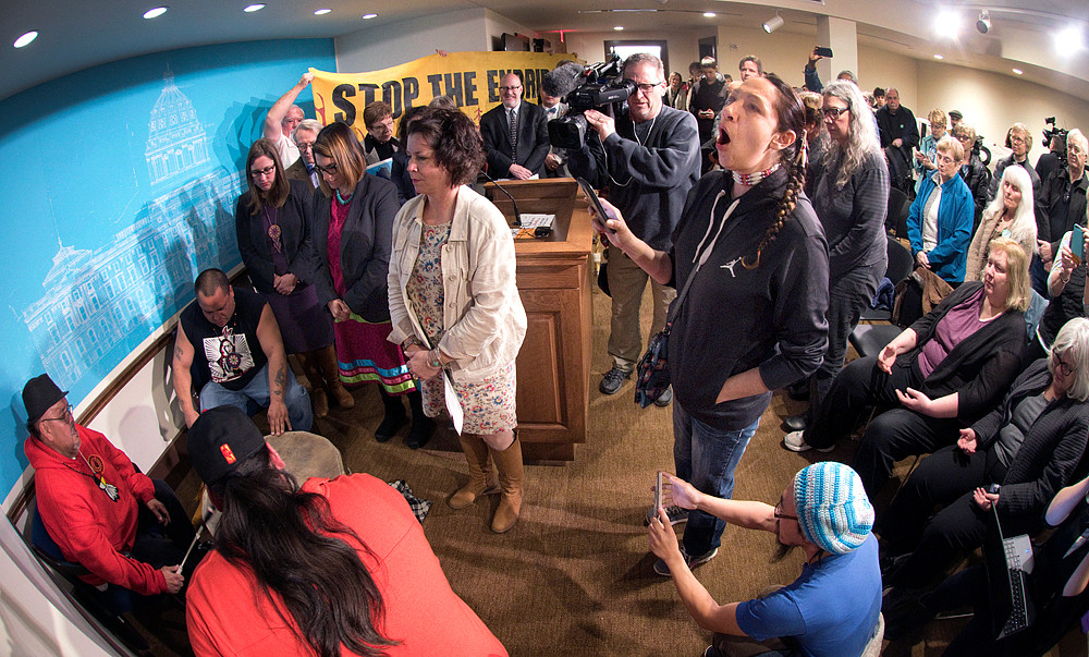 Ana Quad, Cloud Women, right, sings as the SouthSide Ramblers, left, drum prior to a news conference of concerned citizens, Indigenous leaders and legislators in opposition to changes to pipeline permitting in the Omnibus Energy Bill before the House of Representatives.
