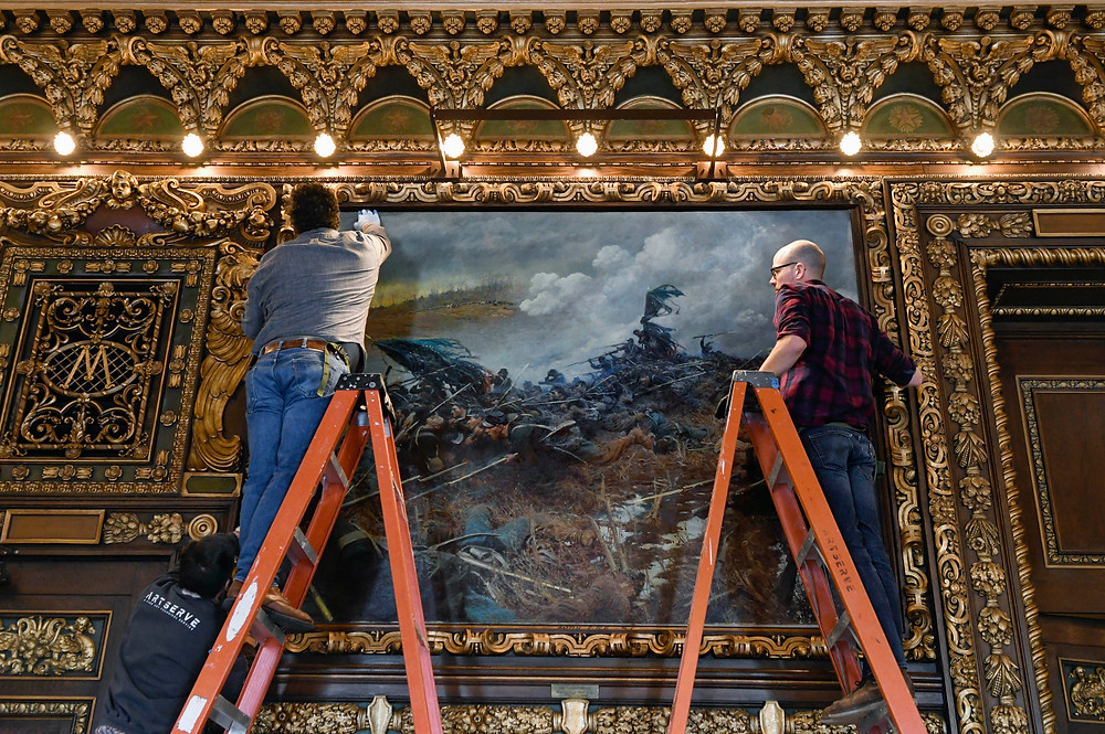 """ArtServe staff, from left, Mark Friedl, Garth Thompson and Dave Reimers rehang """"The Battle of Nashville"""" in its original place on a wall in the Governor's Reception Room at the Capitol."""
