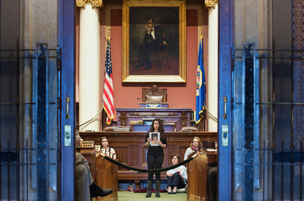 Erin Maye Quade holds the photograph of a gun violence victim and tells their story during her a 24-hour sit-in in the House Chamber to have the House vote on gun control bills.