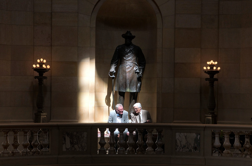 Lobbyists Brian Rice and Andrew Kozak talk on a bench lit by a beam of light from a window at the base of the Capitol's dome.