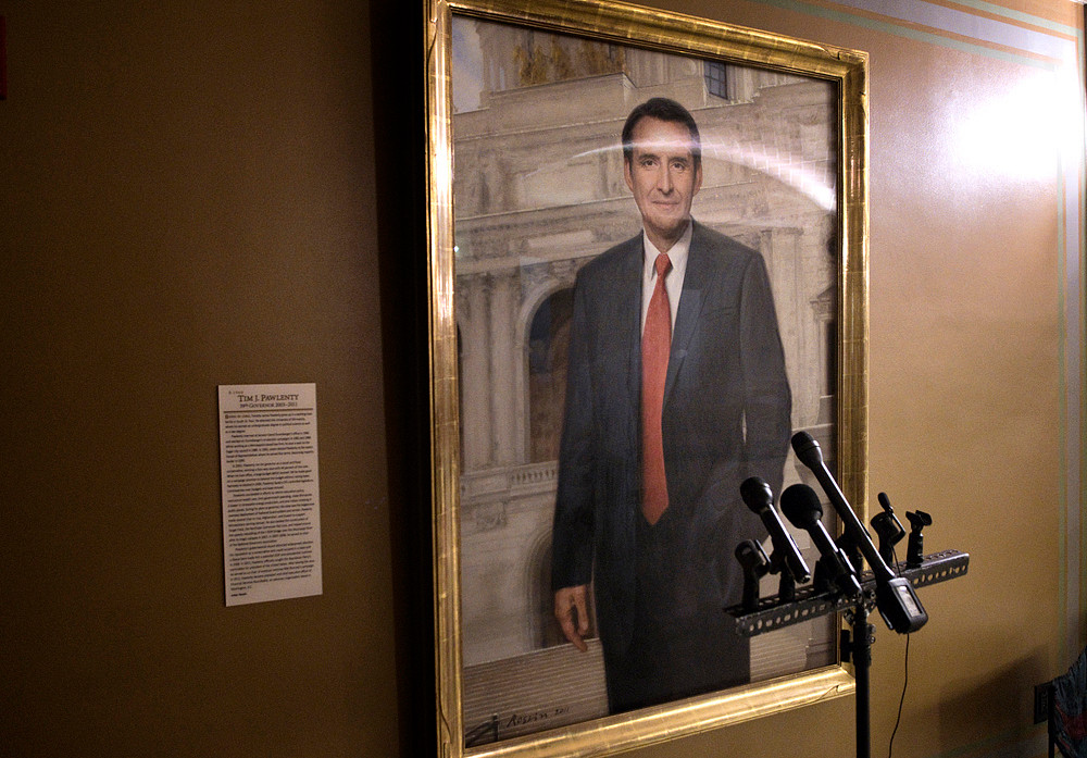 Microphones that will be used by legislative leaders and Gov. Mark Dayton when they emerge from end of session negotiations are stored in front of the portrait of former Gov. Tim Pawlenty. It giving the appearance that the former governor is ready to give a speech.